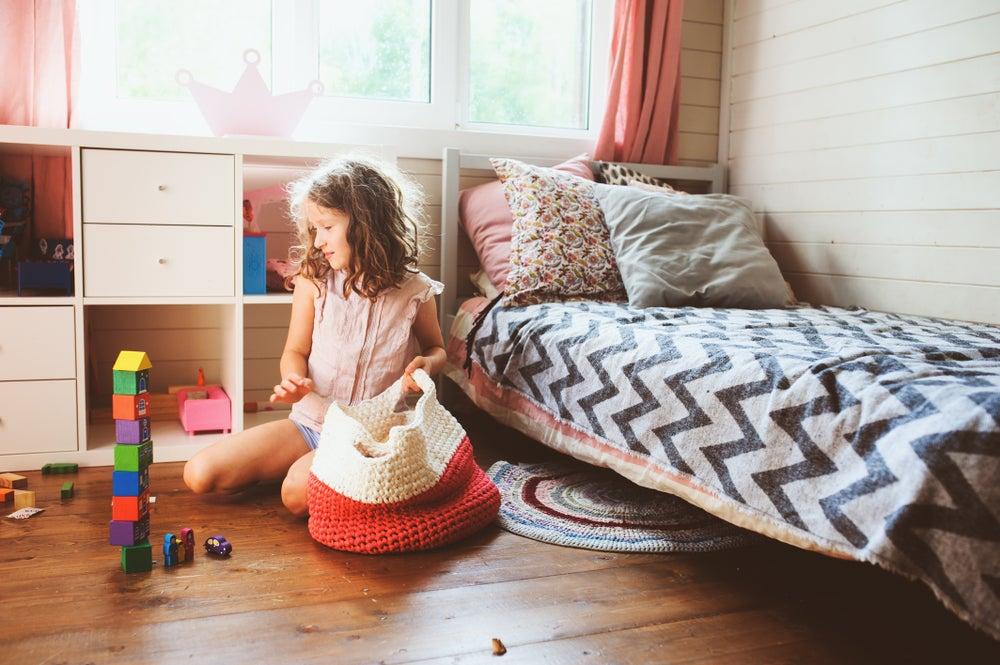 Niña pequeña ordenando su habitación.