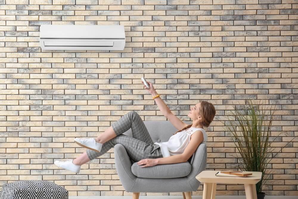 Mujer activando el aire acondicionado.