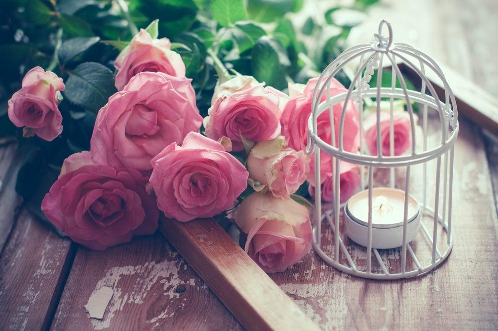 Jaula con flores y una vela.