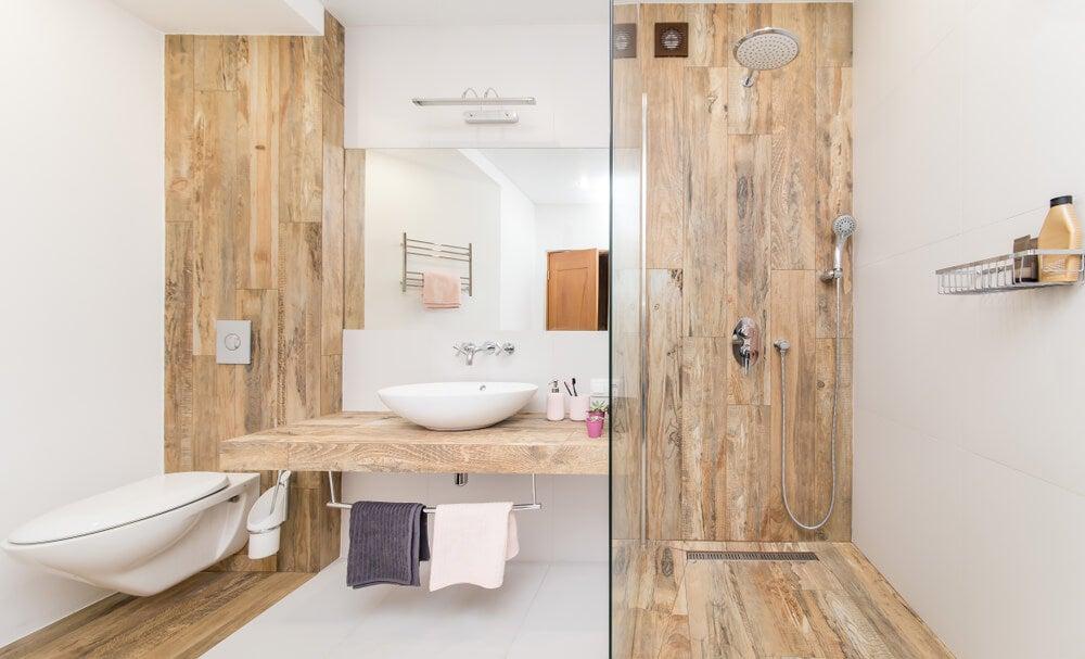 Baño de piedra blanca y madera clara.