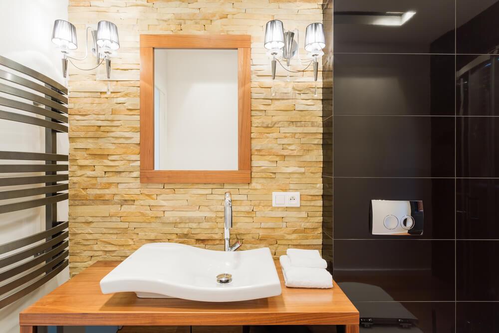 Baño de piedra con detalles en madera.