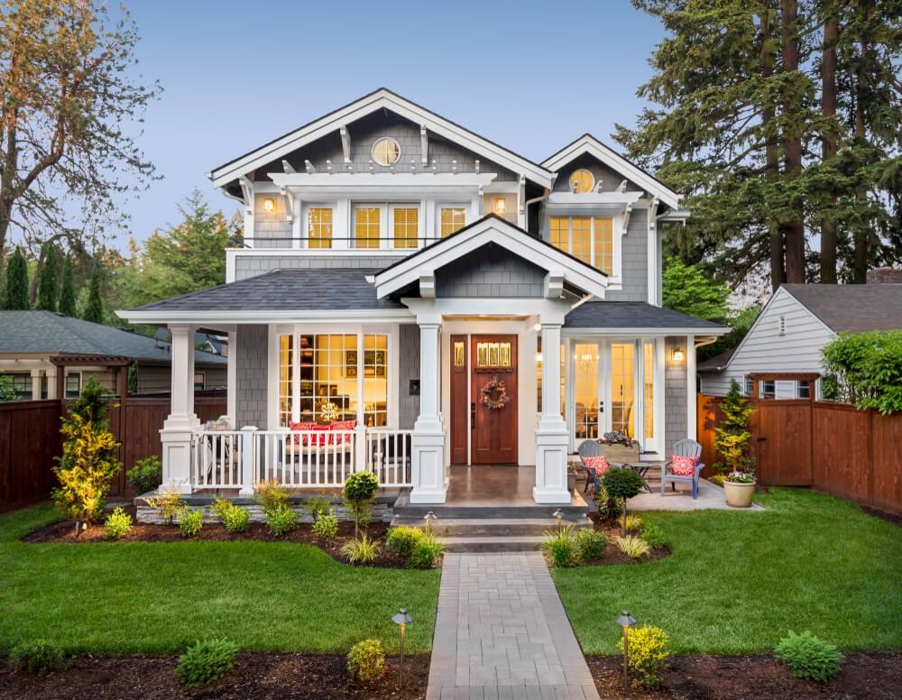 Jardines y porche de una casa de estilo Hamptons.