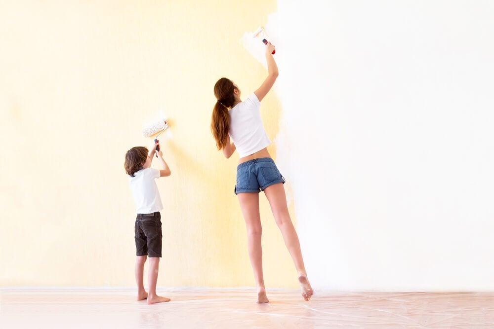 Madre e hijo pintando una pared de casa.