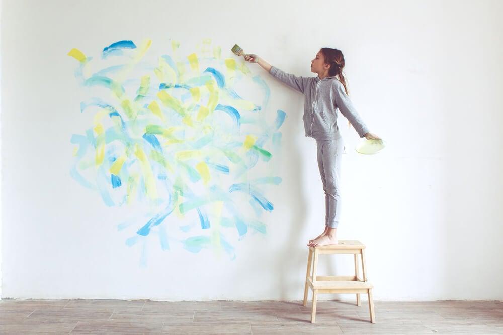 Niña pequeña pintando una pared.
