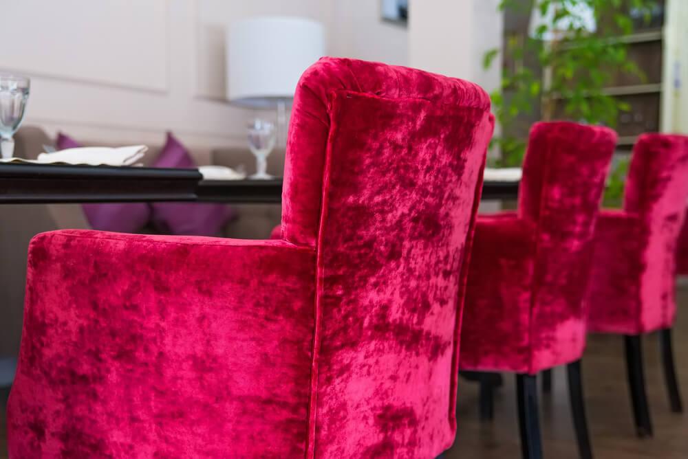 Sillas tapizadas en terciopelo rojo.
