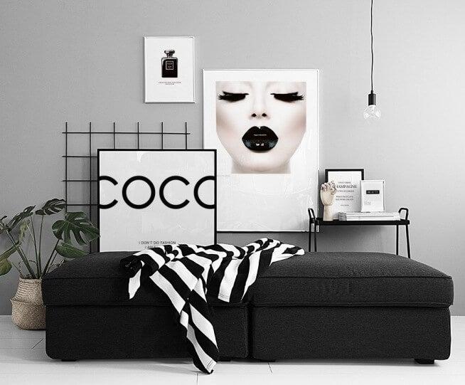 Cuadro Coco sobre sofá negro.
