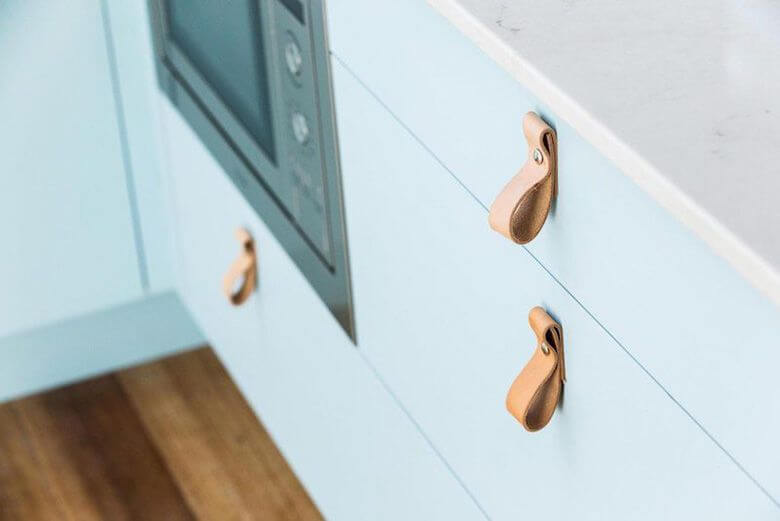 Horizontal leather handles for kitchen drawers.