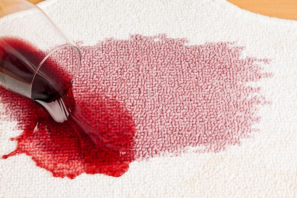 Vino tinto sobre alfombra.