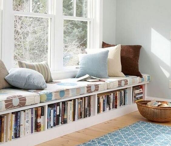Banco con libros al lado de la ventana.
