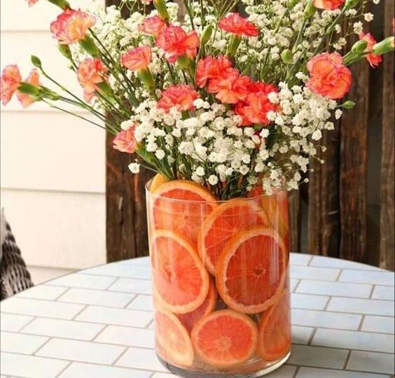Centro de mesa hecho con fruta y flores.