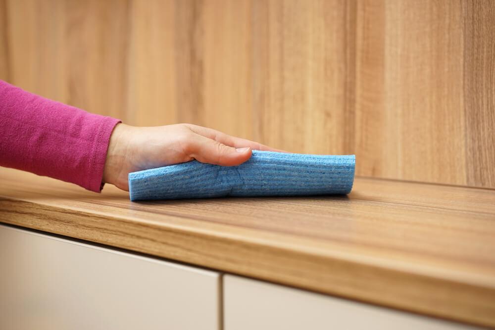 Limpiar polvo del mueble de madera.