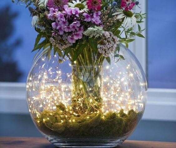 Centro de mesa con luces y flores.