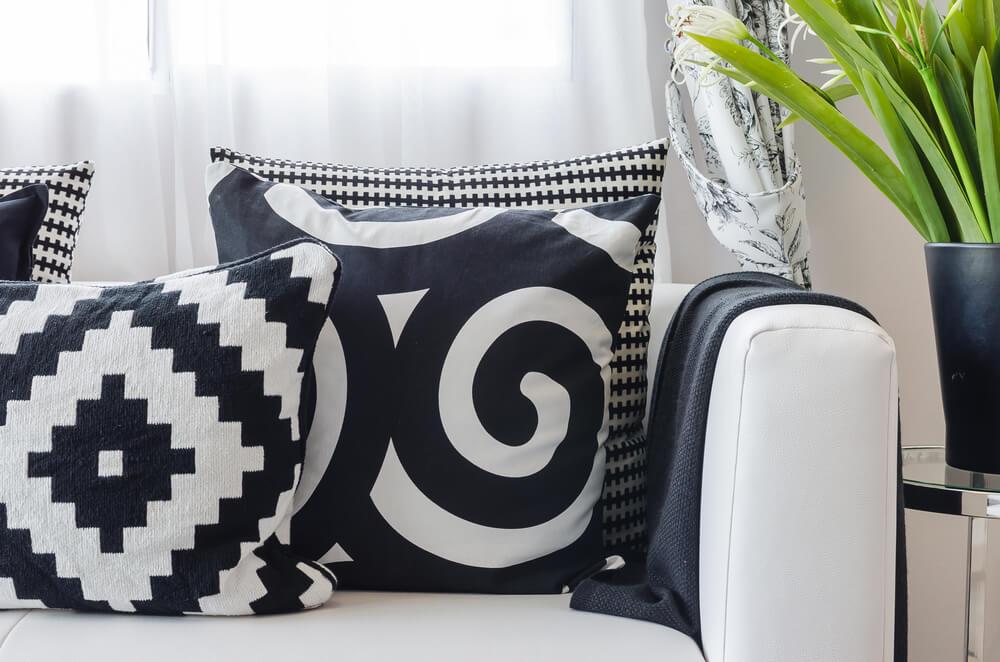 Sofá blanco con cojines negros.