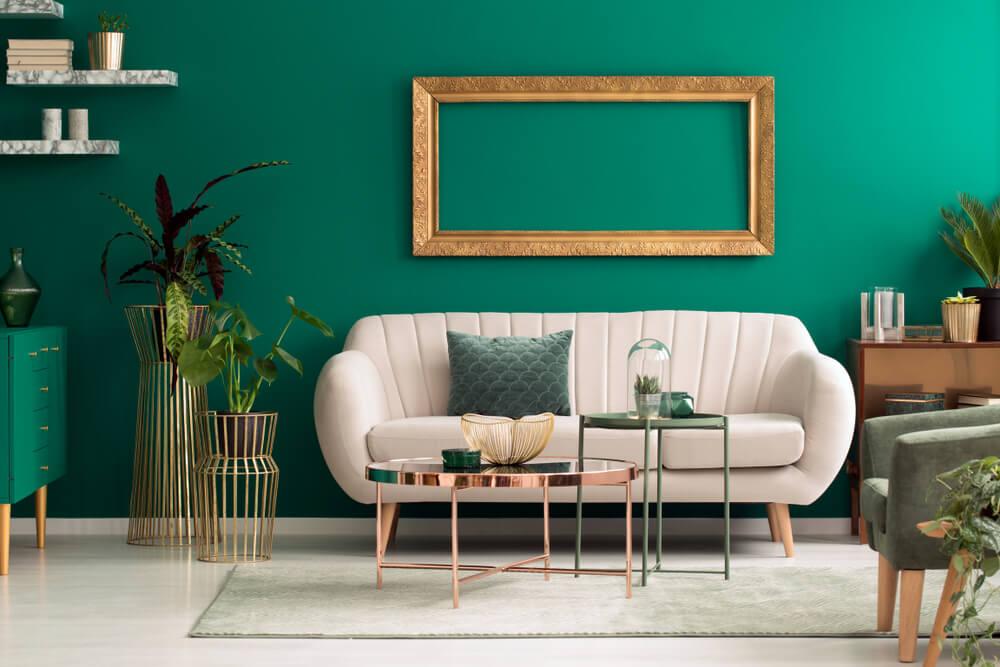 Sofá beige con pared verde detrás.