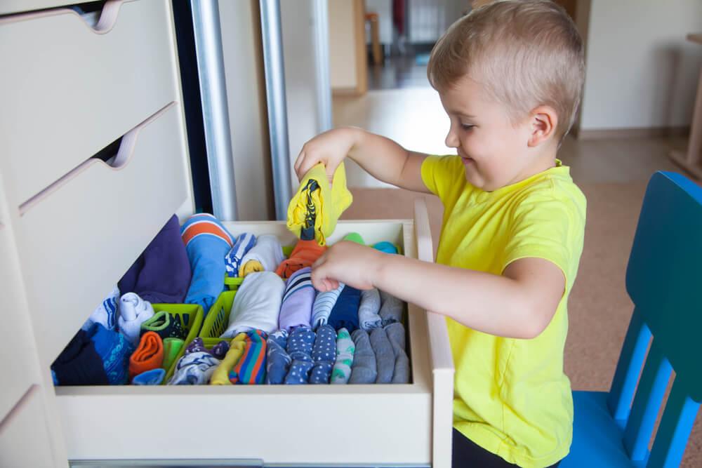 Niño guardando su ropa.