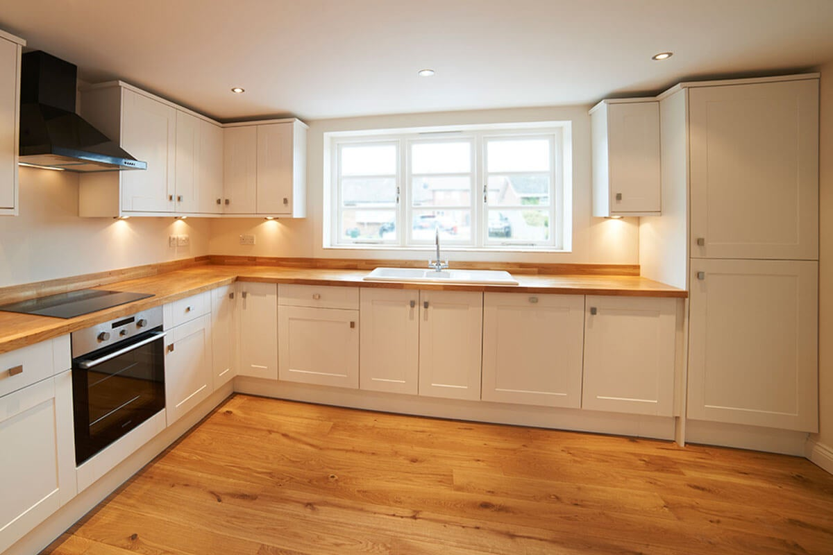 The wooden floor goes very well with the white kitchens.