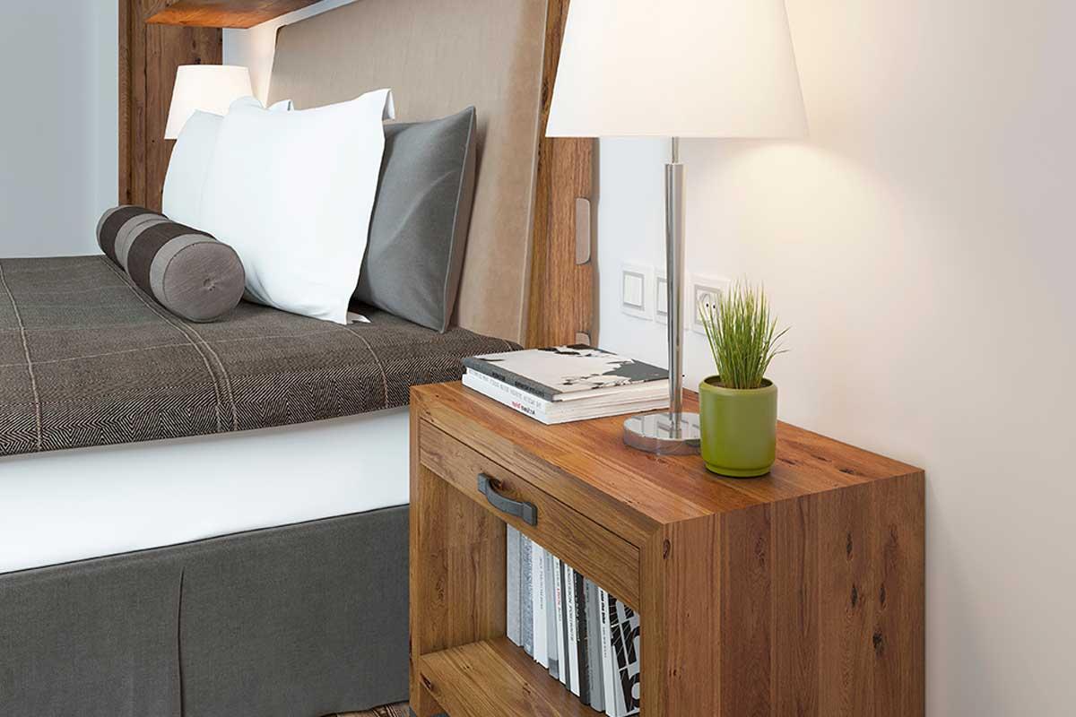 Coloca una mesa de noche en tu cama de hotel en casa.