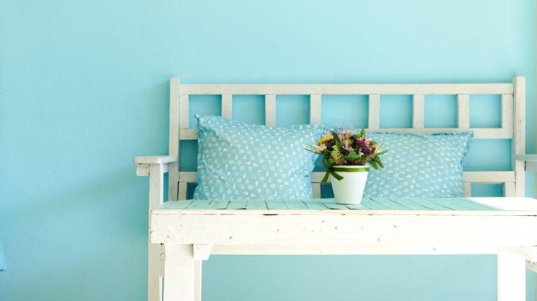 panchina con cuscini e muro azzurro