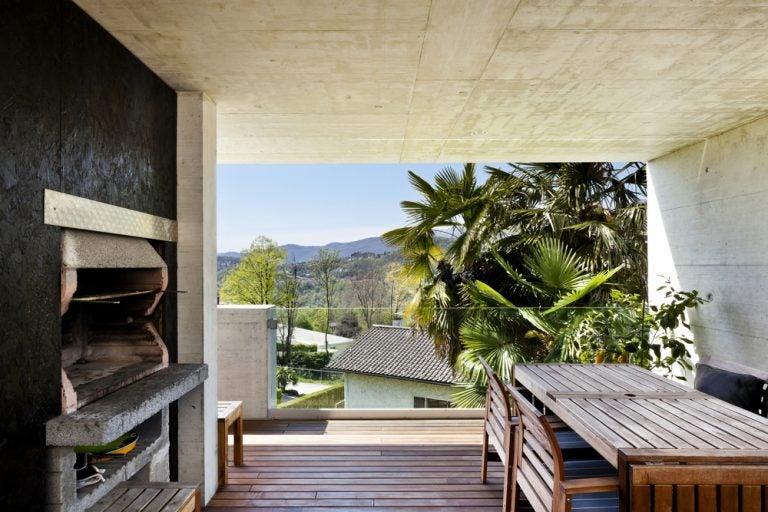 spazio esterno con parquet e forno in pietra con tavoli e sedie in legno
