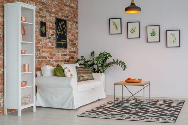 soggiorno con divano bianco e parete in mattoni
