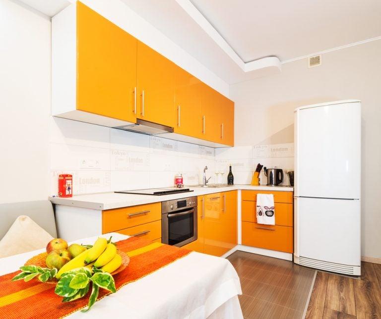 cucina in arancio con tavolo e frutta