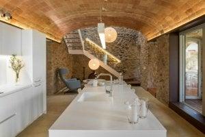 cucina bianca con soggiorno e parete in pietra