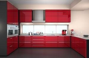 Cucina rossa abbinata al pavimento nero.