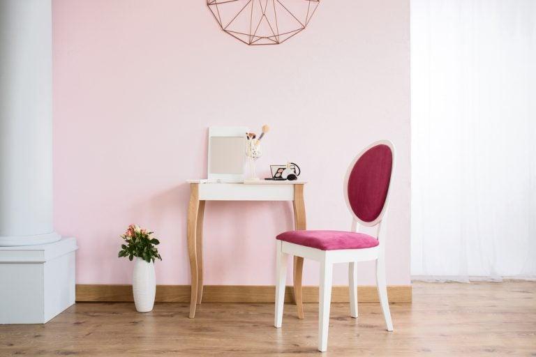 muro rosa con tavolino e sedia