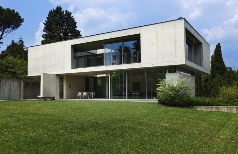 casa con facciata in calcestruzzo con finestre e giardino