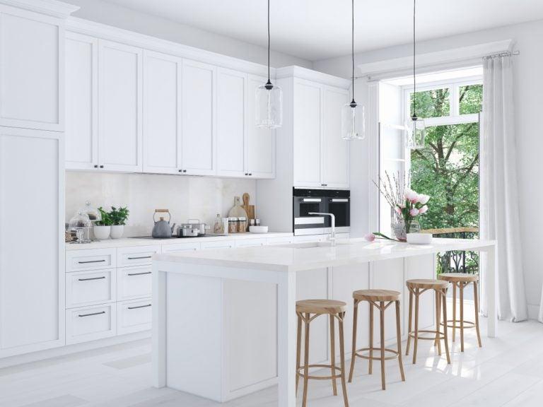 cucina con bancone e sgabelli in bianco