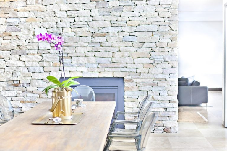 soggiorno con tavolo sedie e muro in pietra