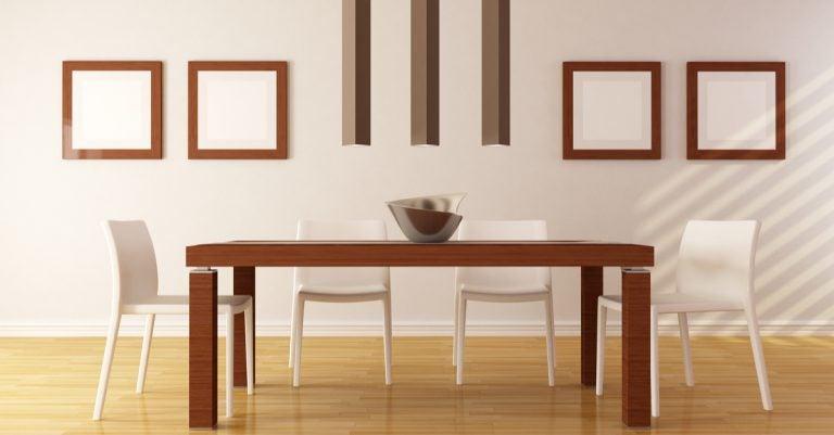 sala da pranzo con sedie bianche e tavolo in legno scuro