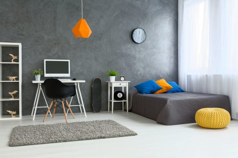 Camera da letto con scrivania, sedia e tappeto.