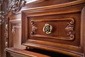 Maniglia dorata a forma di rosa per un armadio vintage in legno.