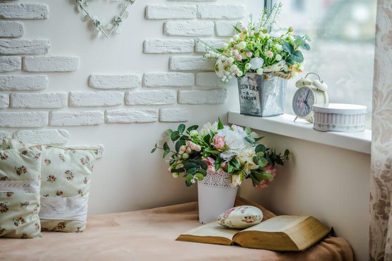 angolo lettura accostato contro la parete con cuscini e fiori