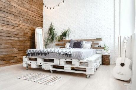 stanza con parete in legno e letto su piattaforme di legno bianche
