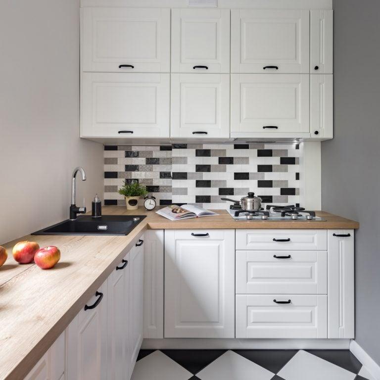 cucina bianca con piano lavoro in legno chiaro e mattonelle bianche e nere