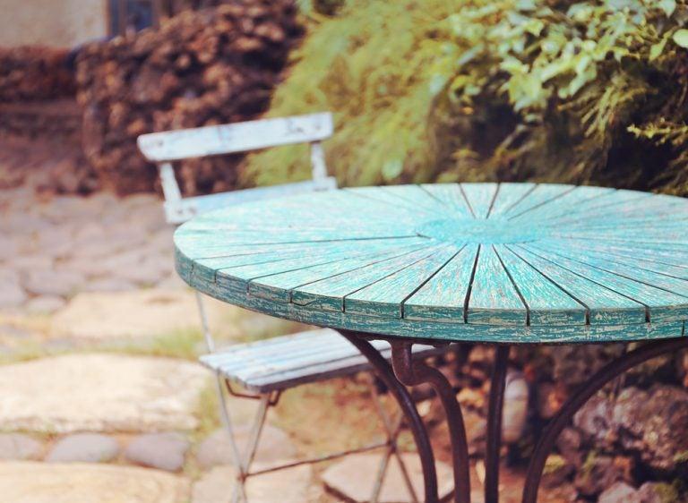 giardino con tavolo in legno azzurro con base in metallo e sedia