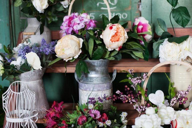 vasi di latta con fiori colorati su mensole di legno