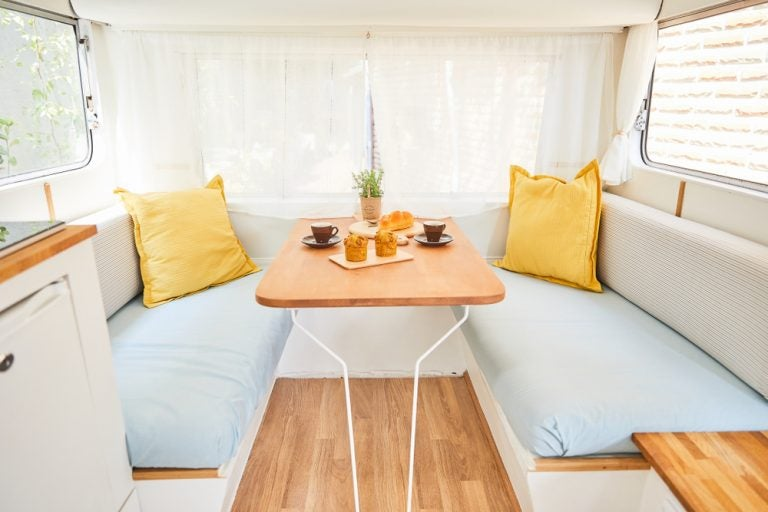 Interno di una roulotte con tavolino e sedute comode