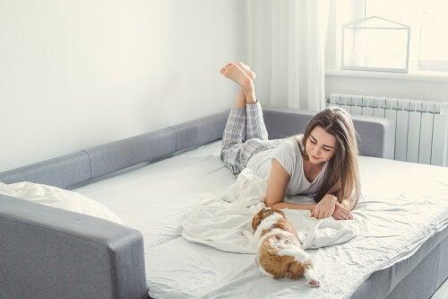 Bambina gioca su letto con peluche