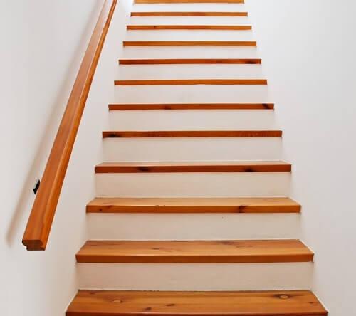 Scala bianca con gradini e passamano di legno