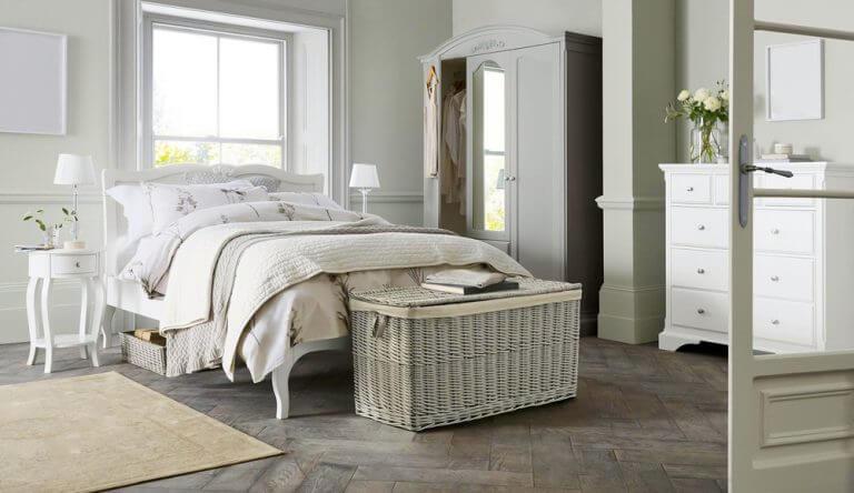 baule vicino al letto in vimini bianco