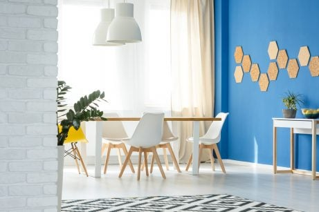 Salotto con mura colorate e arredamento in bianco e legno