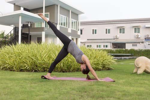 Ragazza fa yoga in giardino