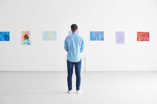 Visitatore guarda dipinti in un museo