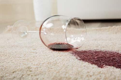 Bicchiere di vino caduto su tappeto