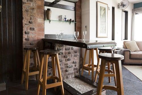 Bancone bar con bicchieri e sgabelli