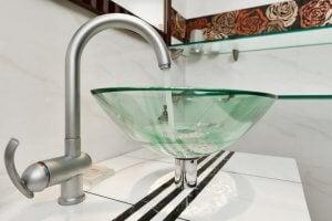 Acqua scorre in un lavandino di vetro
