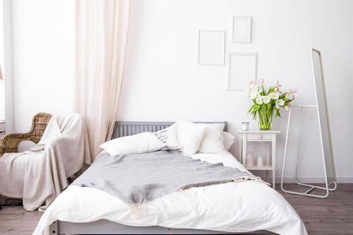 Letto con lenzuola e coperte in materiali naturali